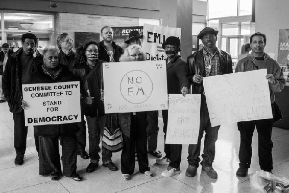 <p>Figure 4.1<br>Members of the FDDL protest changes by EM Darnell Earley to public comment rules. <em>MLive, Flint Journal.</em></p>