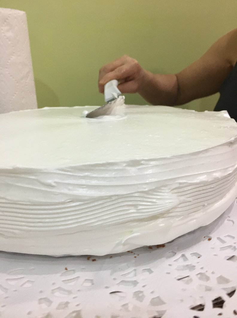 <p>The second step to icing one of her cakes: smooth out the icing (something that I still cannot do well).</p>