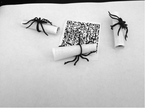 <p>Figure 4.1 Examples of plastic spiders and QR codes that were key ingredients for the Ask Anansi scavenger hunt</p>