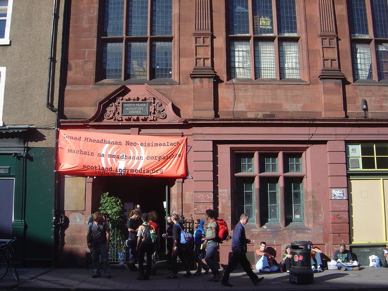 <p>The Independent Media Center (IMC) - Indymedia - is a network of collectively run media outlets established in 1999 to provide grassroots coverage of the World Trade Organization (WTO) protests in Seattle. It distributed up-to-the-minute reports, photos, audio, and video footage through its website. Above, a temporary IMC in Edinburgh covering protests at the 2005 G8 summit. © CC BY-SA 3.0</p>