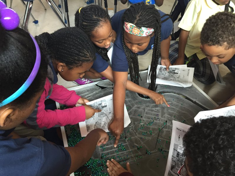 <p>Ripple Effect students using a topographic model and Mardi Gras beads to test predictions and gather evidence about where water collects during a storm. Topographic model provided by Derek Hoeferlin and his students at Washington University in St. Louis.</p>