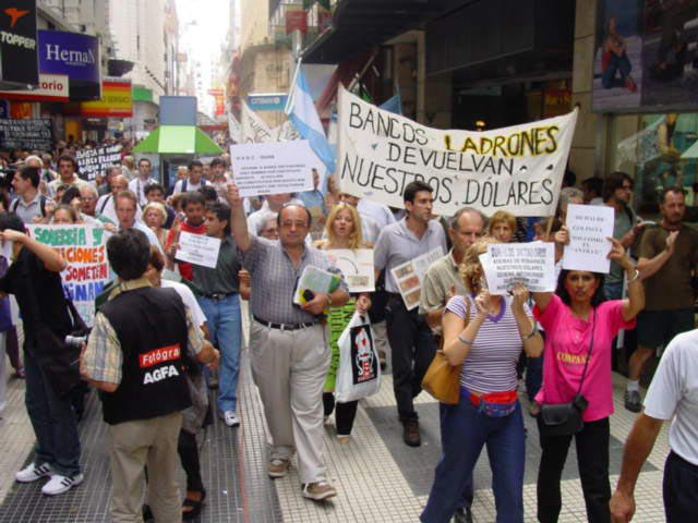 """<p>Horizontalidad was first used by the movements in Argentina, in the wake of the 2001 financial crisis. Above: a protest in Argentina against the banks in 2002. The large sign reads """"Thieving banks - give back our dollars"""". Photo by Pepe Robles Cacerolazo / under CC BY-SA 3.0 license.</p>"""