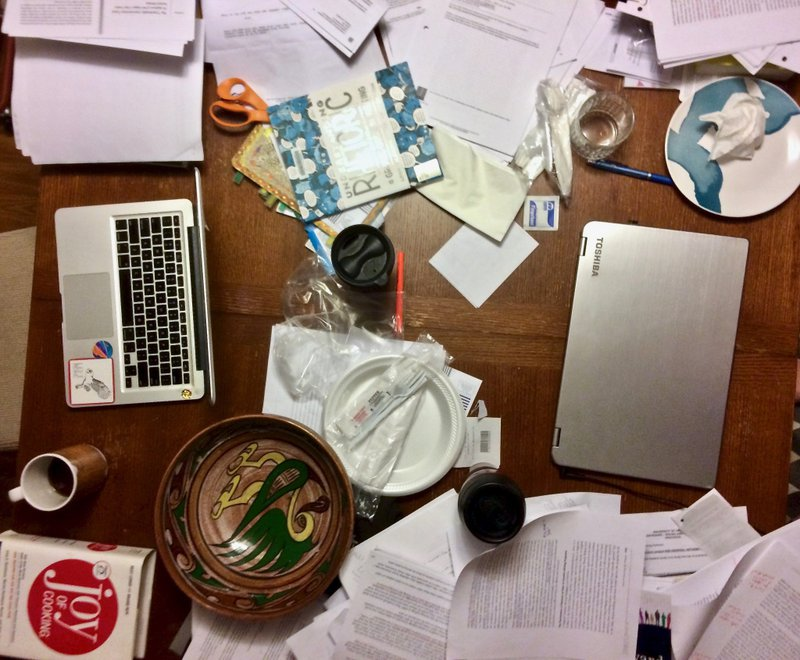 <p>From April 26, 2018: the author's kitchen table as it looked when this article was first composed, scattered with her writing materials (laptop, paper, pens) and everyday ephemera. Copyright, Rhiannon Scharnhorst, 2019.</p>