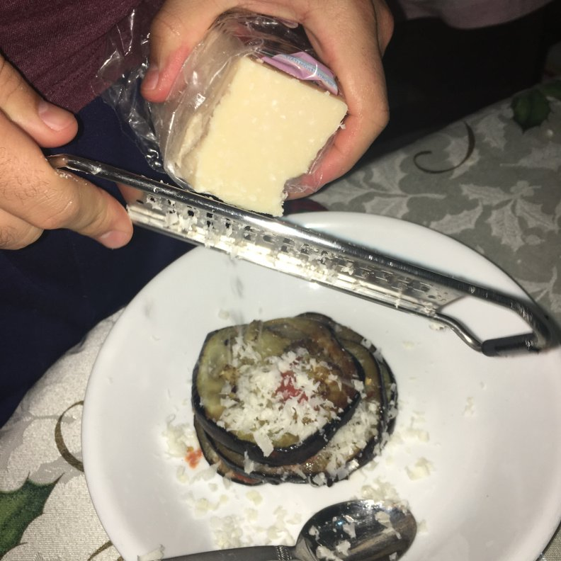 """<p class="""""""">David shredding parmesan onto another layer of his eggplant stack.</p>"""