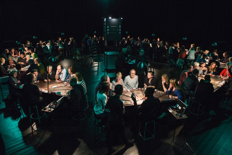 <p>The Belgian theater and performance collective, Ontroerend Goed, greets audiences as co-creators. Above, an immersive theatre piece entitled £¥€$ (LIES), in which audience members play a form of poker. Photo by Thomas Dhaenens and Michiel Devijver.</p>