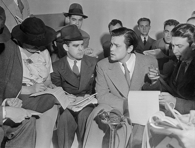 "<p>Orson Welles explains to reporters that no one connected with the ""War of the Worlds"" radio broadcast had any idea the show would cause panic. Photograph in the public domain.</p>"